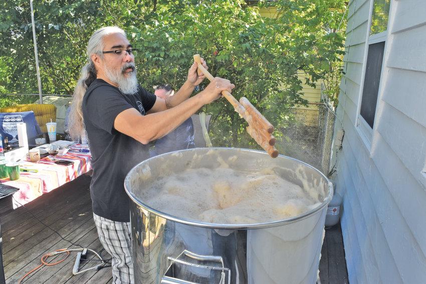 Homebrewer John Frederick stirs a boiling homebrew vat of rye and hops.
