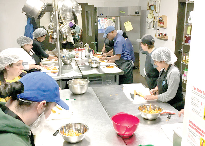 A class at Allen Neighborhood Center learning knife safety and basic knife cuts, before creating a french cuisine dish from scratch. All students are tested and certified with a food handlers license upon graduation.
