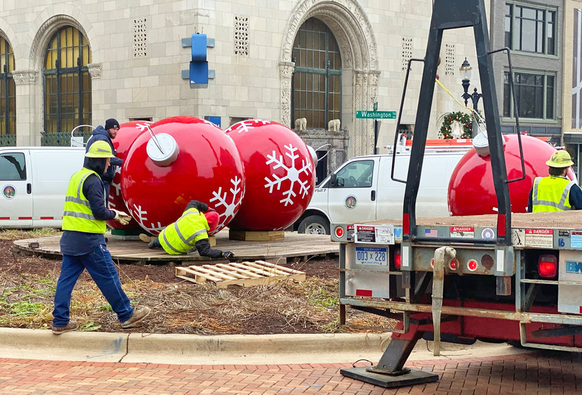 BWL workers installing the repaired Christmas ornaments.