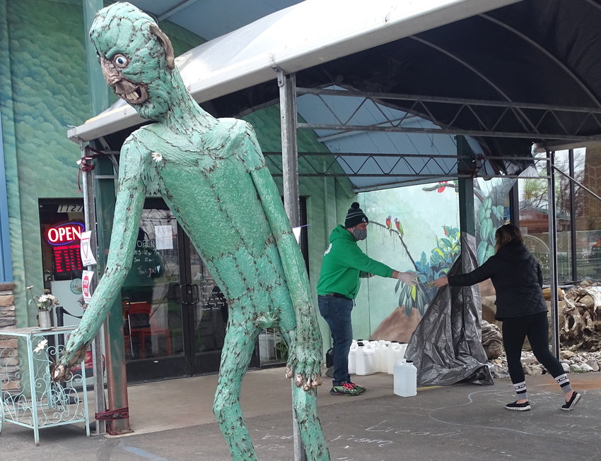 A 15-foot-tall swamp creature enforces social distancing in the parking lot of Preuss Pets, where customers are still picking up food and medicine for their furred, feathered and scaled companions.