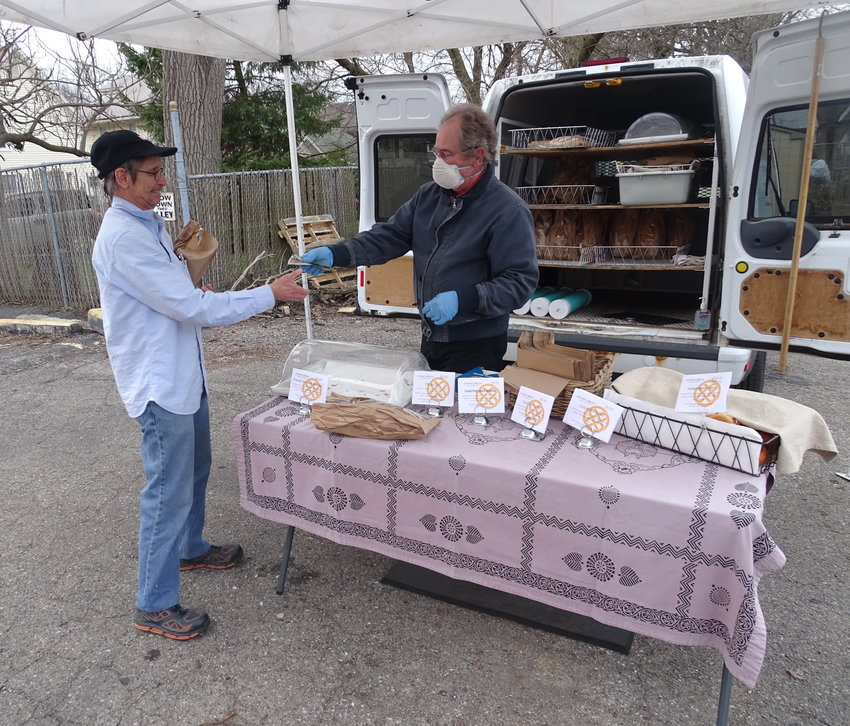A customer picks up baked goods from vendor Kevin Cosgrove of Stone Circle Bakehous at the April 1 Allen Farmers' Market. The market is resuming operations April 22 after a two-week hiatus.