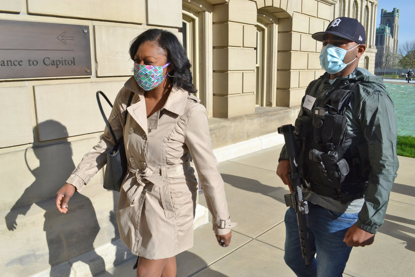 Michael Lynn Jr. and other armed citizens escorts State Rep. Sarah Anthony into the State Capitol.