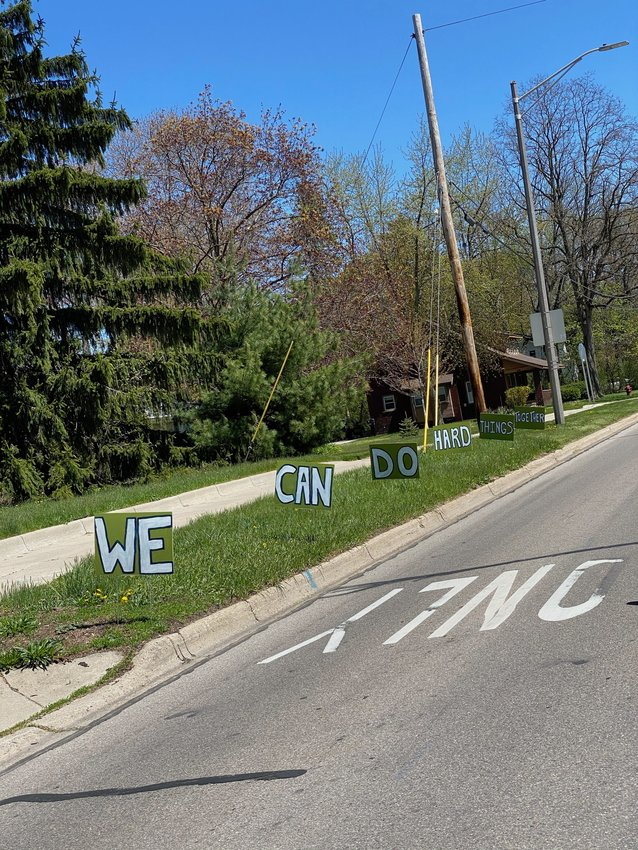 """""""We can do hard things together,"""" say signs along Grand River Avenue near Hagadorn Road in East Lansing."""