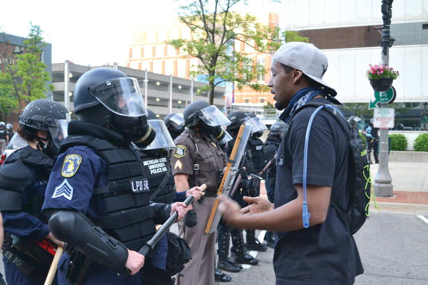 A protester speaks to a police officer on Washington Square after the first round of tear gas had cleared.