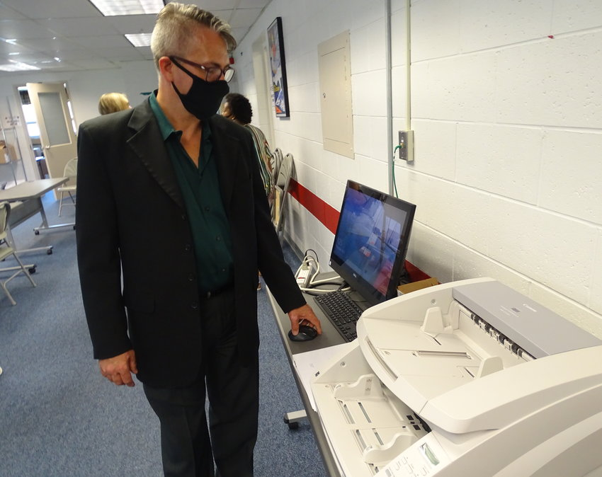 Lansing City Clerk Chris Swope communes with a scanner he'll use on Election Day to process absentee ballots.