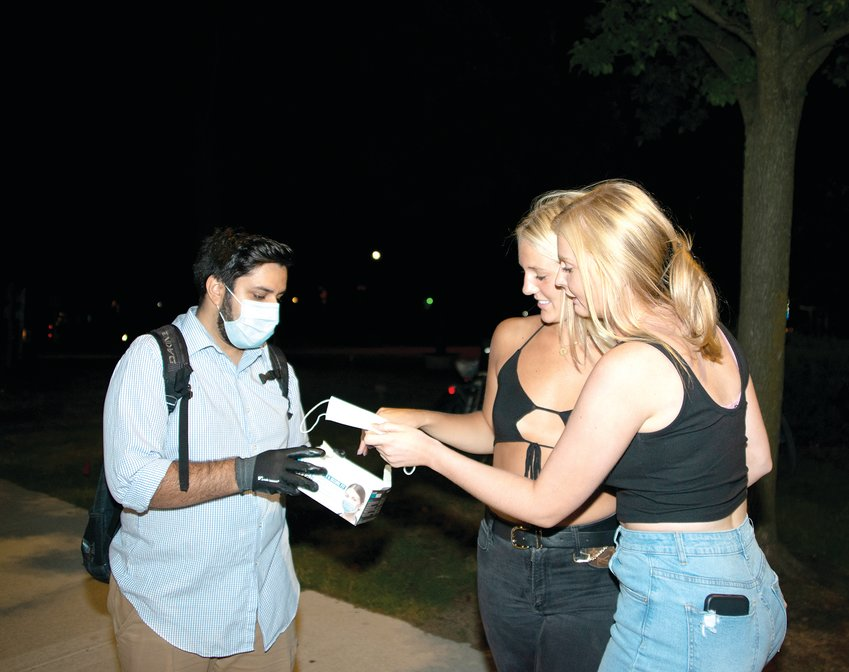 East Lansing Mayor Aaron Stephens hands out disposable face masks to party-goers in downtown East Lansing on Saturday night of Welcome Weekend.