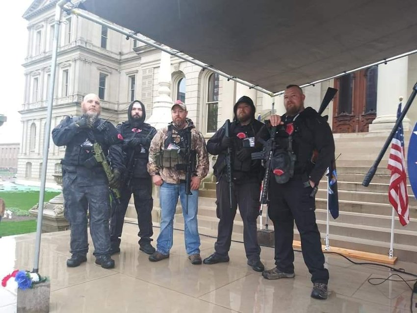 """Five members of the Michigan Liberty Militia pose for a photo on the steps of the Capitol April 30 during protests against Gov. Gretchen Whitmer's lockdown orders. From left, MLM Commander Phil Robinson, two unidentified individuals, William """"Bill"""" Null and Michael """"Mike"""" Null, twin brothers from Plainwell and Shelbyville. The Nulls have been charged in the alleged plot against the governor."""