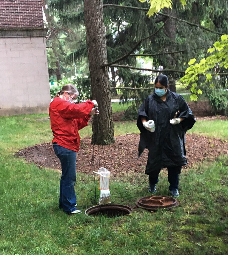 Researchers Becca Ives and Nishita D'Souza pull wastewater out of a manhole for sampling.