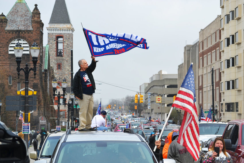 """A man waves a Trump flag atop his vehicle at the April 15, 2020 """"Operation Gridlock"""" protest."""
