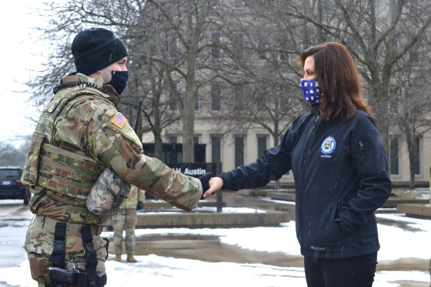 Gov. Gretchen Whitmer shakes hands with a member of the National Guard.