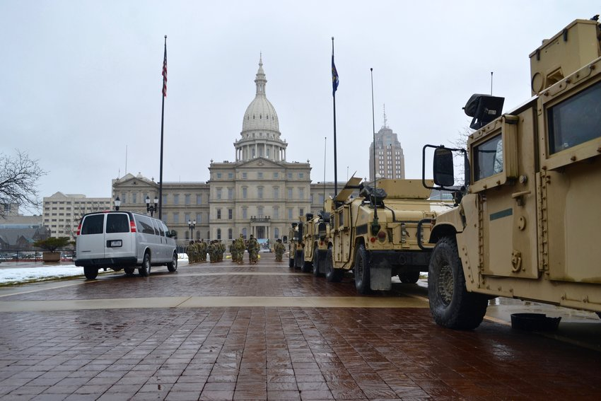 A row of National Guard vehicles lined up behind the Capitol.