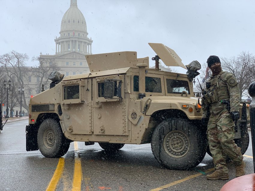 A soldier with the National Guard stands near the downtown traffic circle on Michigan Avenue on Sunday.