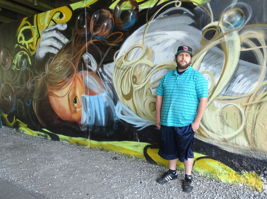 "Artist Isiah Lattimore's pandemic-themed mural under the I-496 overpass on Lansing's River Trail depicts St. Cecilia, the patron saint of music, ""tired"" but ""not dead."""