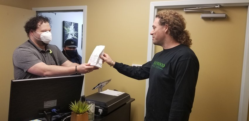 Owner Jeffrey Hank checks out a customer at Edgewood Wellness.