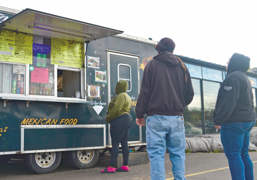 Customers wait to order food at the Taquero Mucho food truck on Cedar Street.