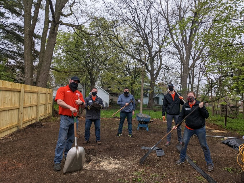 Habitat for Humanity Capital Region volunteers work on a landscaping project for Lansing homeowners and Iraqi refugees, Fatima and Salah.