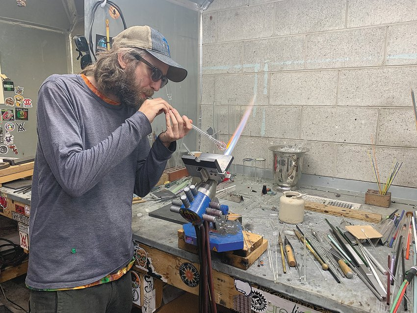 Ben Birney demonstrates a glassblowing   technique at his studio north of Lansing, which he opened about a decade ago largely out of a desire share his artwork with the local community.