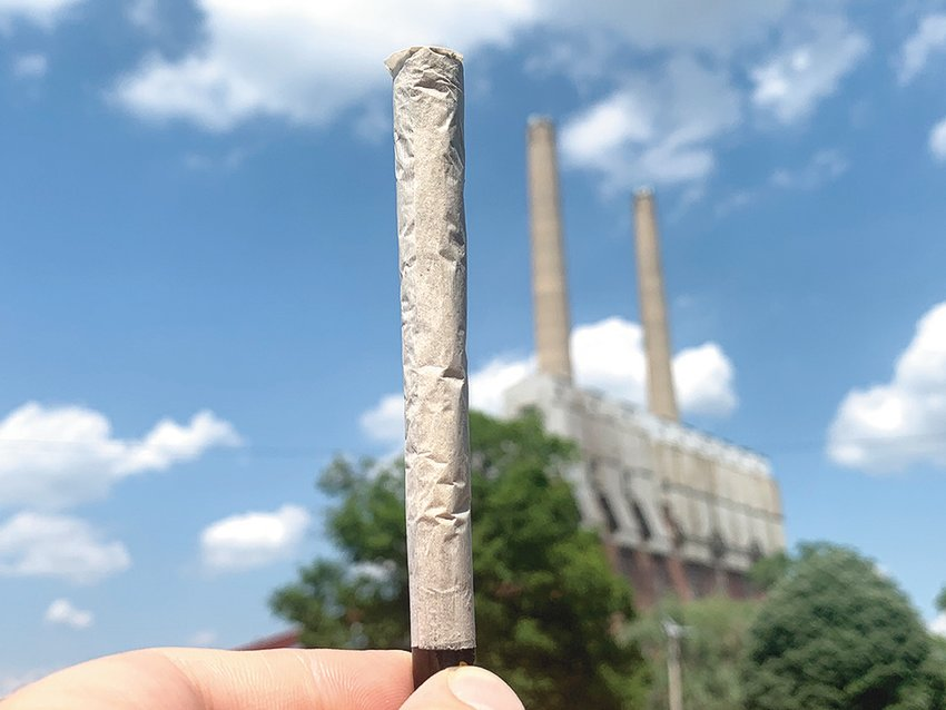 Marijuana from First Class Cannabis Co. rolled neatly into a joint and presented alongside Lansing's famous Otto C. Eckert Municipal Power Plant.