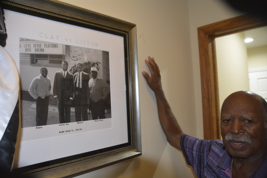 Gregory Eaton with the photo of him, Muhammad Ali, Malcolm X and his uncle.