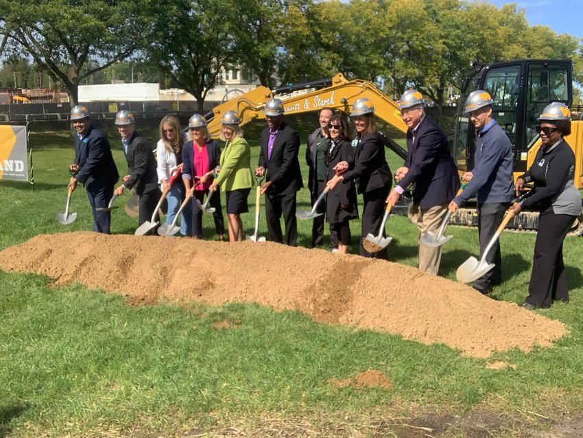 Partners in the development of a new universally accessible playground at Adado Riverfront Park line up for a groundbreaking ceremony.