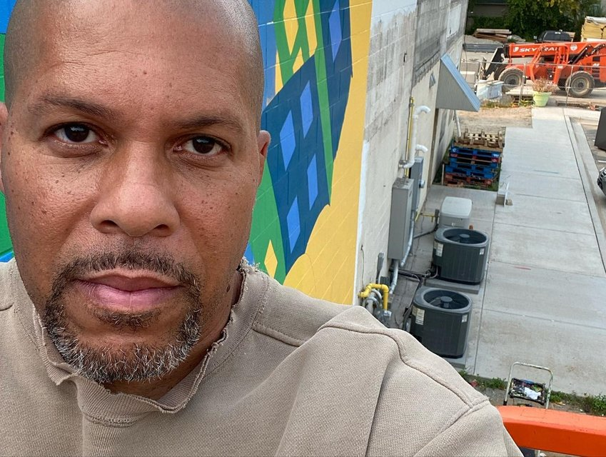 Artist Brian Whitfield takes a selfie at the site of his latest mural at the Allen Neighborhood Center on Kalamazoo Street.
