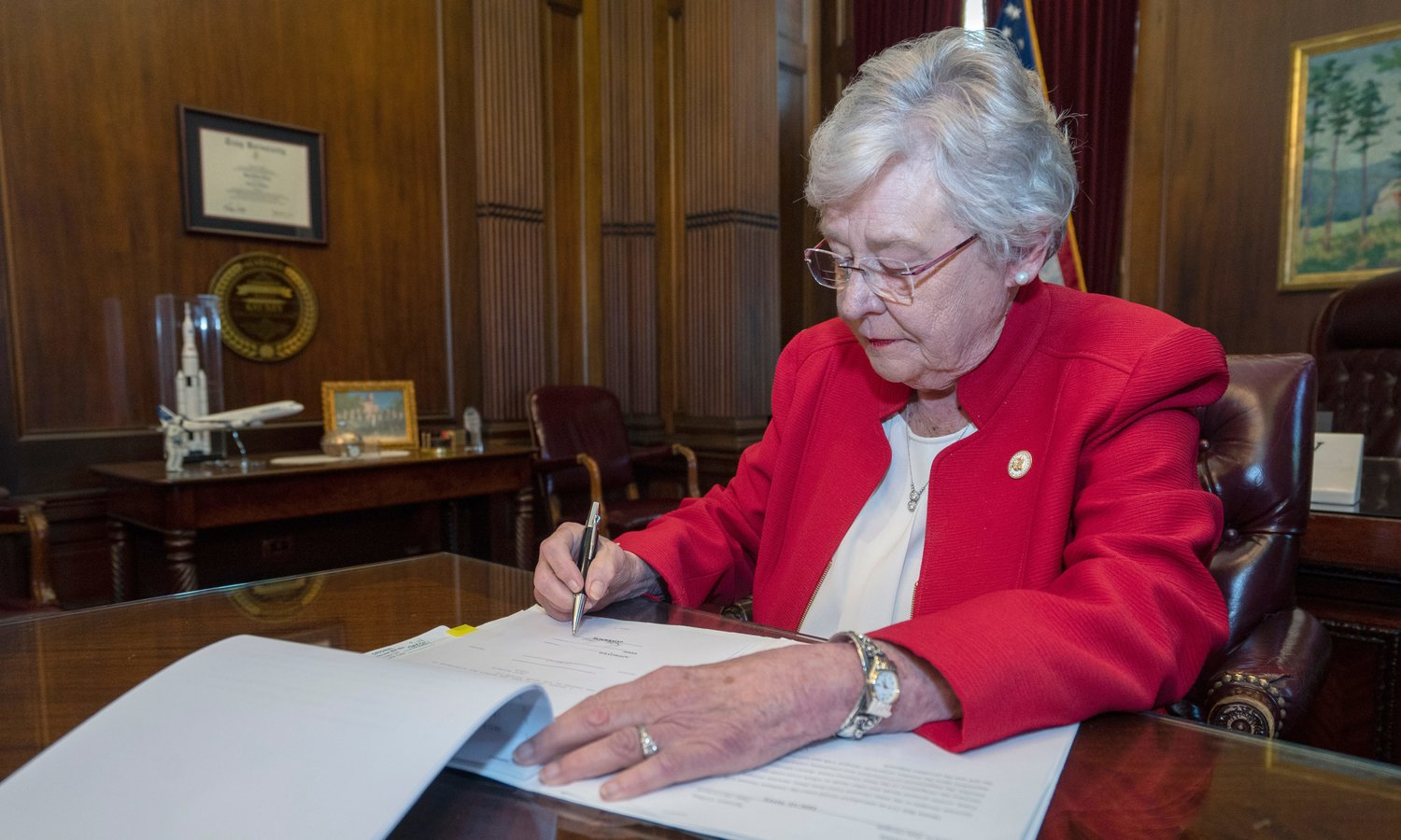 Gov. Kay Ivey signing the nation's harshest abortion law.