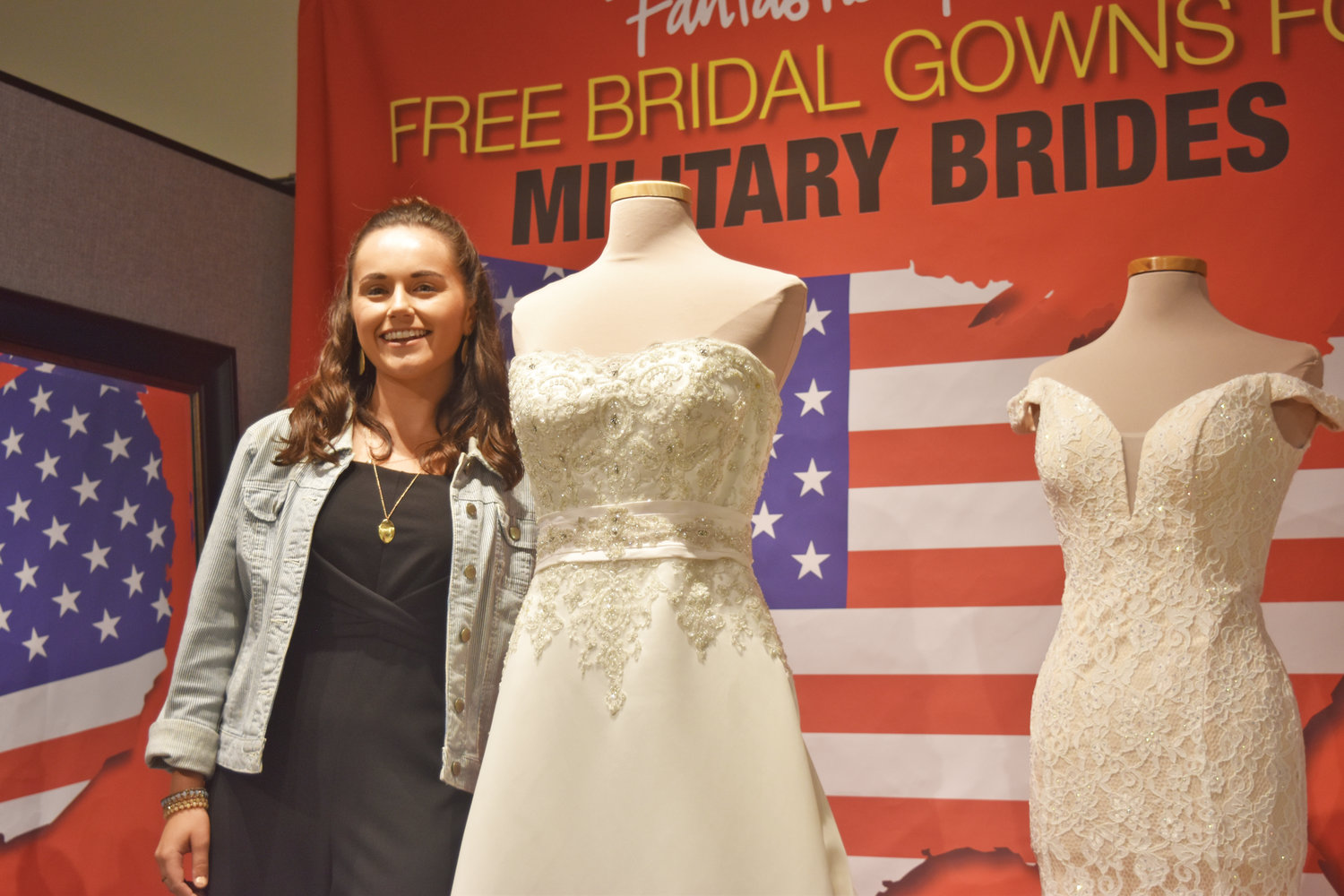 Holly Reed, Fantastic Finds marketing manager, poses next to a giveaway dress to a military bride.