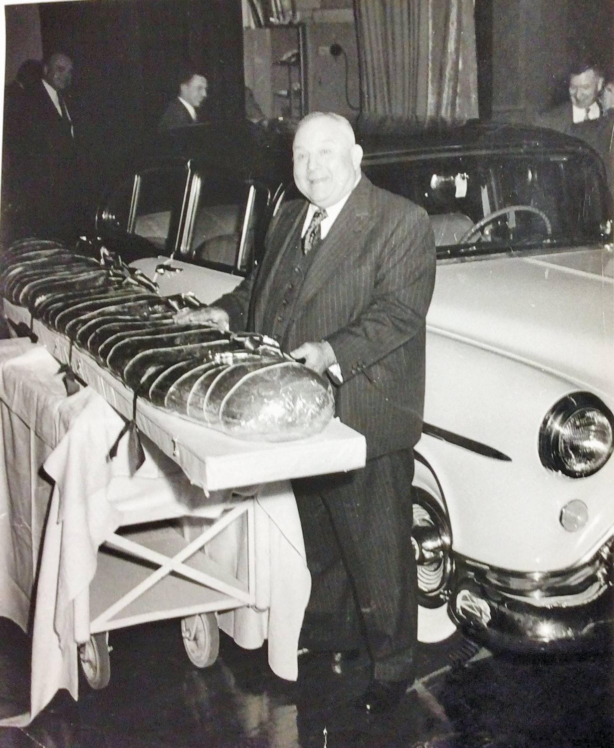 Ralph Young, MSU's longest-serving athletic director, at his retirement party in 1954 with his gifts — a new car and a 147-pound sandwich.