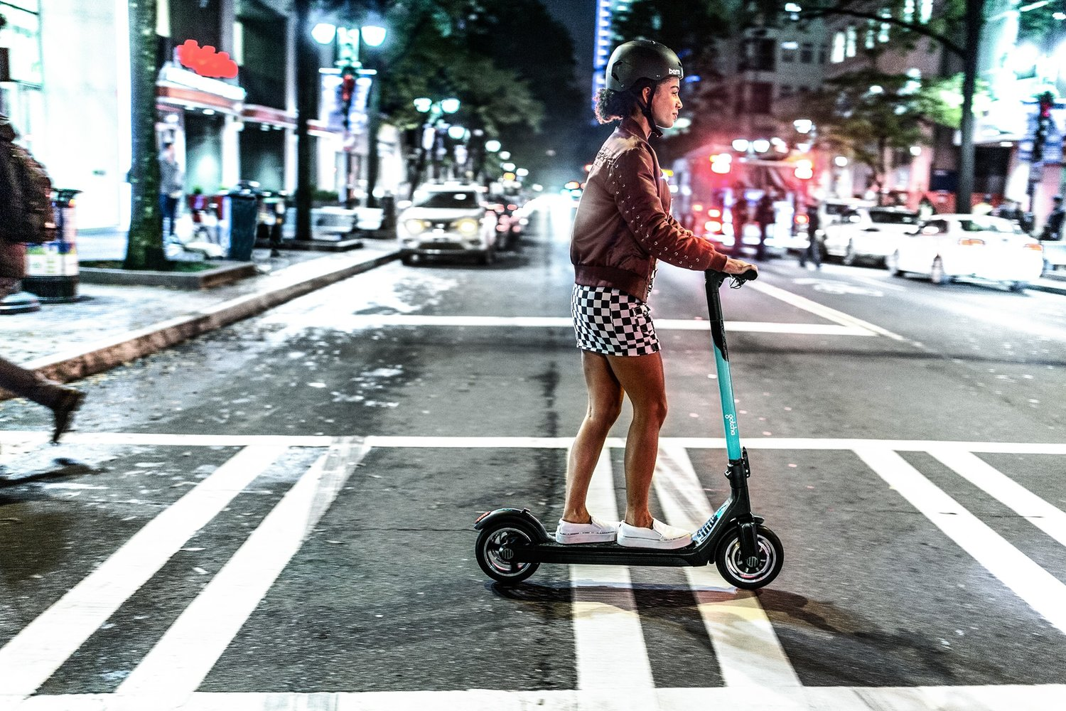 Promotional image of a woman riding a Gotcha scooter on a city cross-walk.