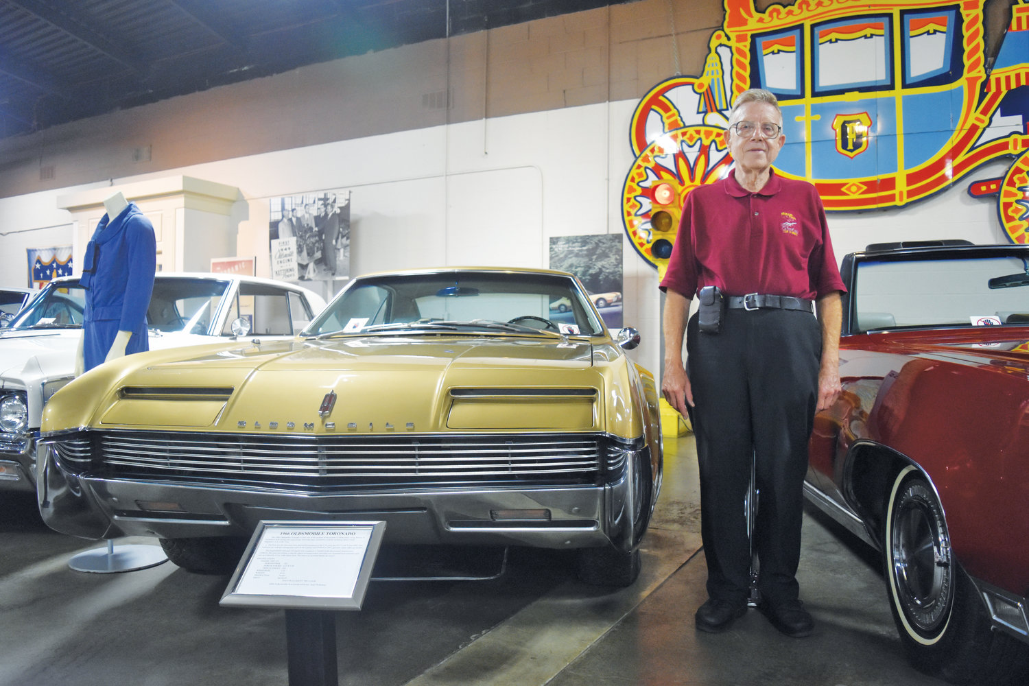 R.E. Olds Transportation Museum volunteer Jerry Garfield stands next to a 1966 Oldsmobile Toronado.