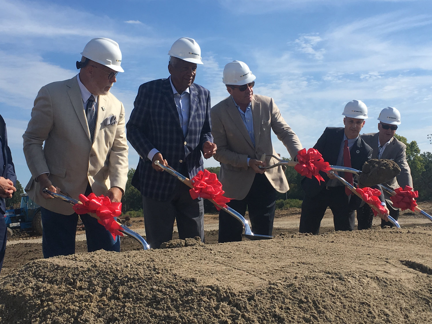 Drain Commissioner Pat Lindemann (left), Developer Joel Ferguson, former Mayor Virg Bernero, Mayor Andy Schor and Christopher Stralkowski, the executive project manager for Ferguson Development LLC, participate in a ceremonial groundbreaking event for the Red Cedar Development project.