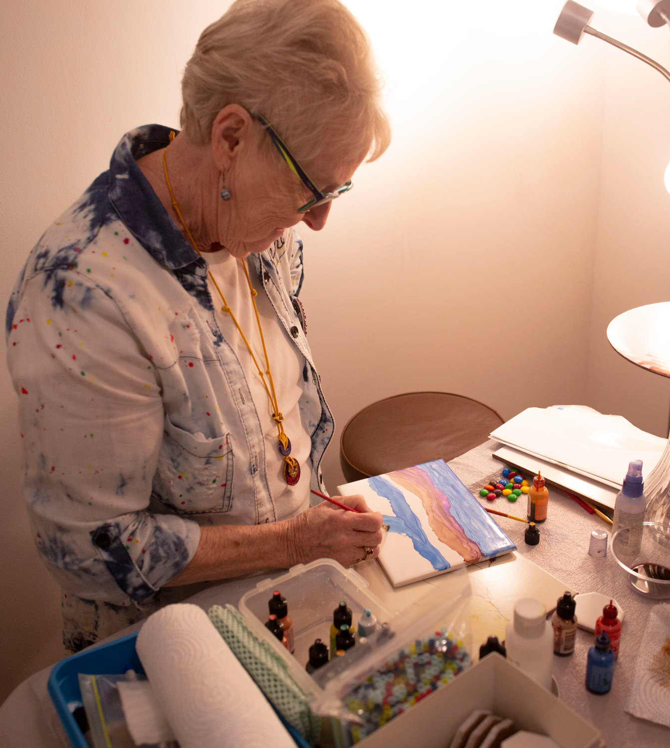 Helene Murray giving a demonstration of the alcohol-ink art, where she paints with inks and sprays alcohol to great texture and patterns on titles.