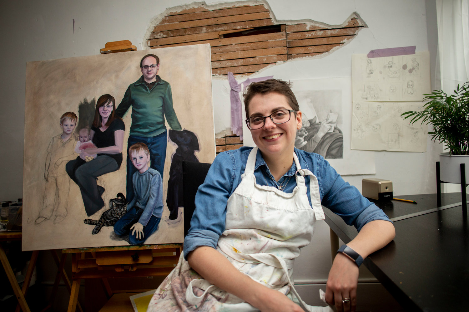 Emily Kibbe in her studio space at Cedar Street Art Collective where she recreates portraits of families and their loved ones.