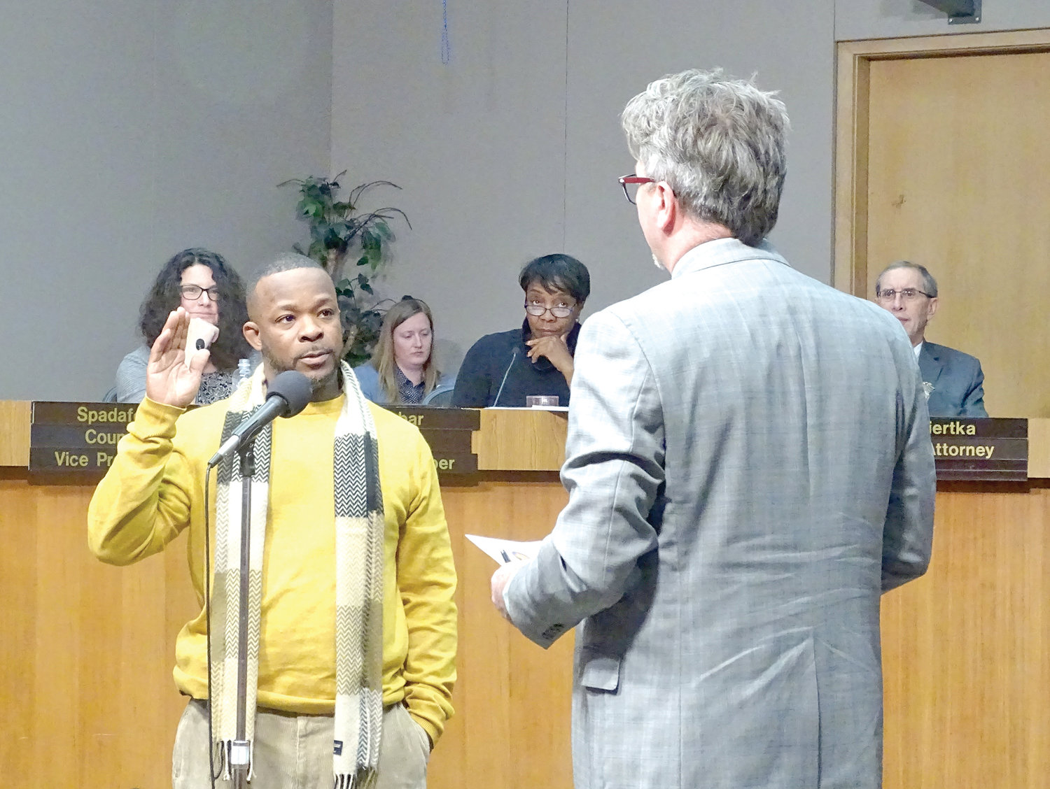 Lansing City Clerk Chris Swope (right) swears in Deshon Leek as the Third Ward commissioner for the Board of Water & Light at Monday's City Council meeting.