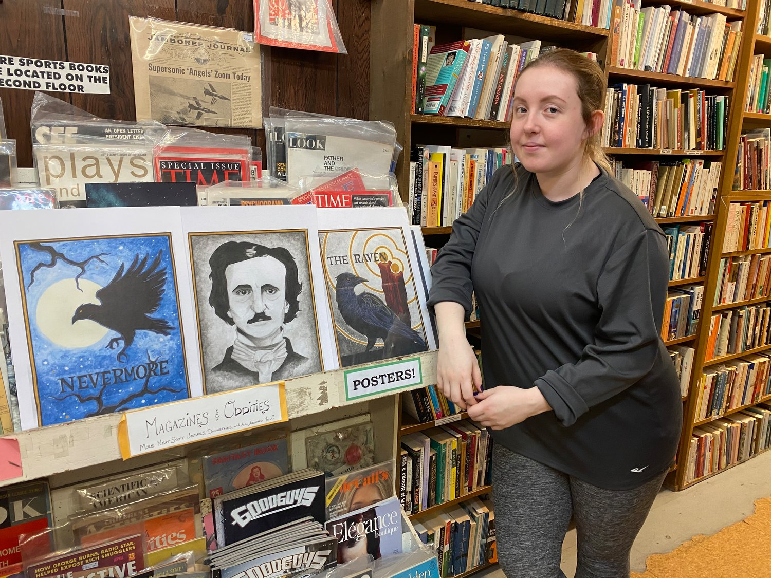 "Artist Jesse Chastain stands next to her original ""Poe"" inspired illustrations, which are available for sale at Curious Book Shop."