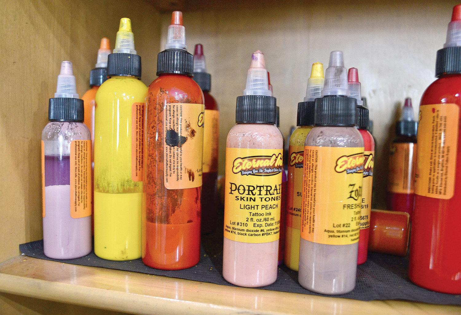 A smattering of ink bottles rests on a shelf at Eclectic Art Tattoo Gallery.