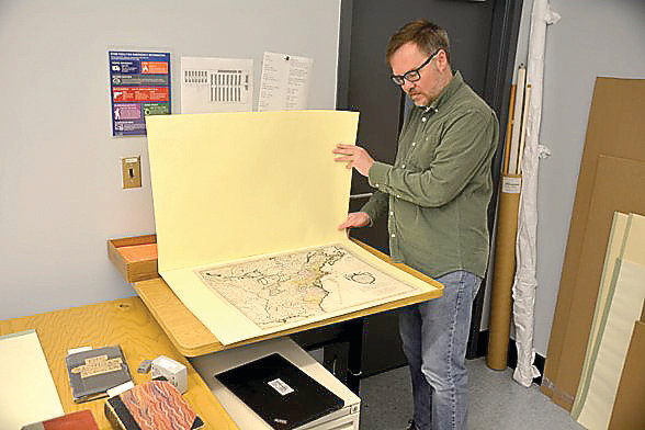 Library of Michigan's head of Special Collections, Timothy Gleisner, inspects an 18th century map of Michigan.