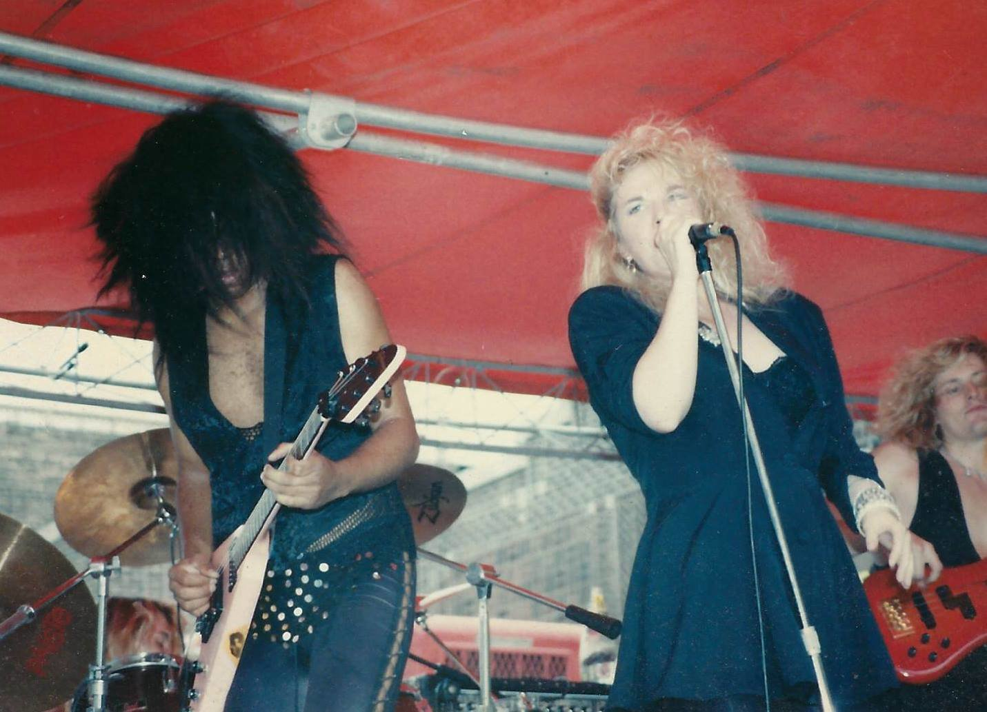 Craig Calvert and Jan James performing onstage together with the glam metal band Jewel Fetish in the mid-'80s.