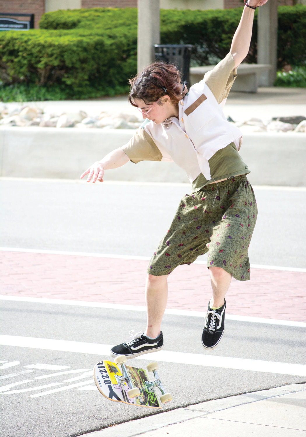 Madeline Smith, 23, does a kickflip over a sidewalk on Michigan Avenue.