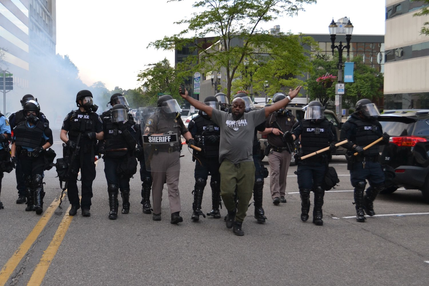 A man is pushed along by police.