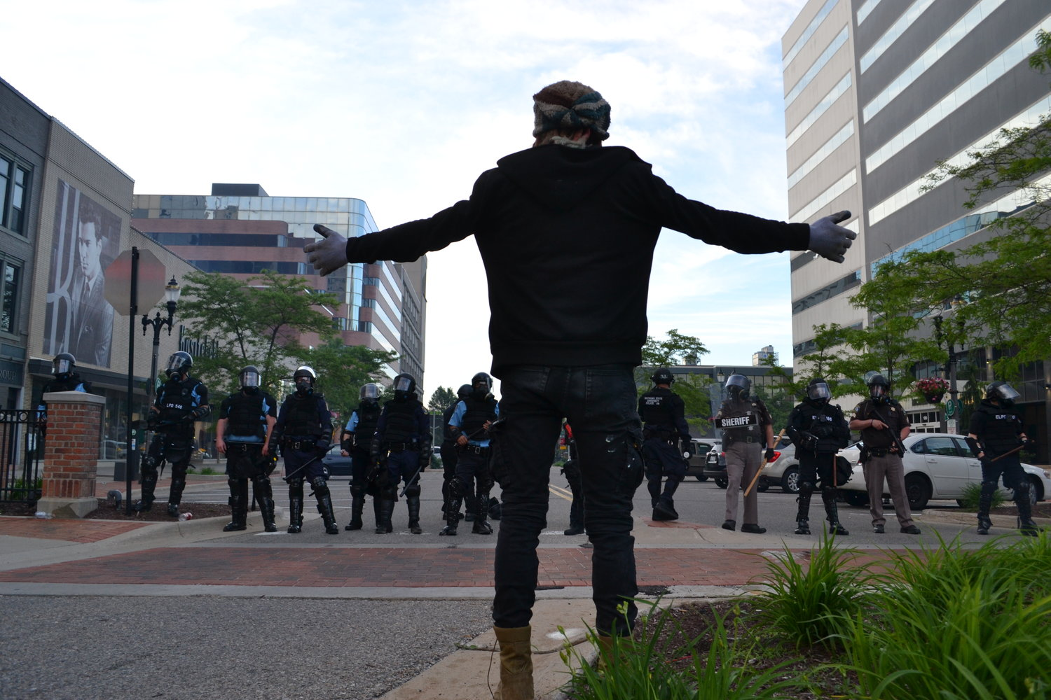 A protester confronts a lineup of police.