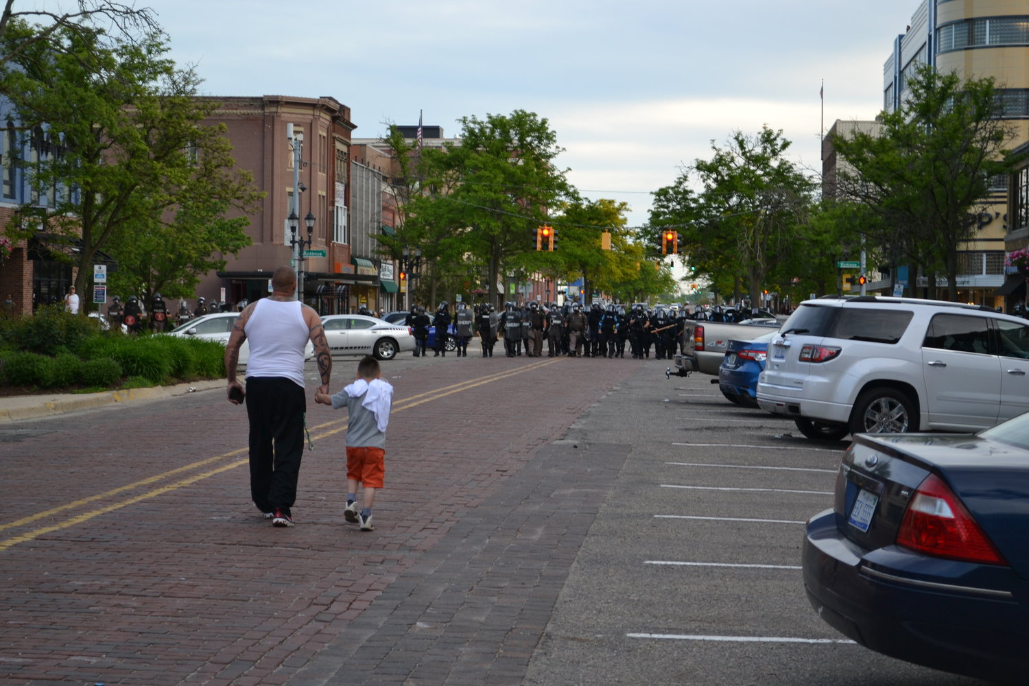 A man approaches a lineup of police with his son.