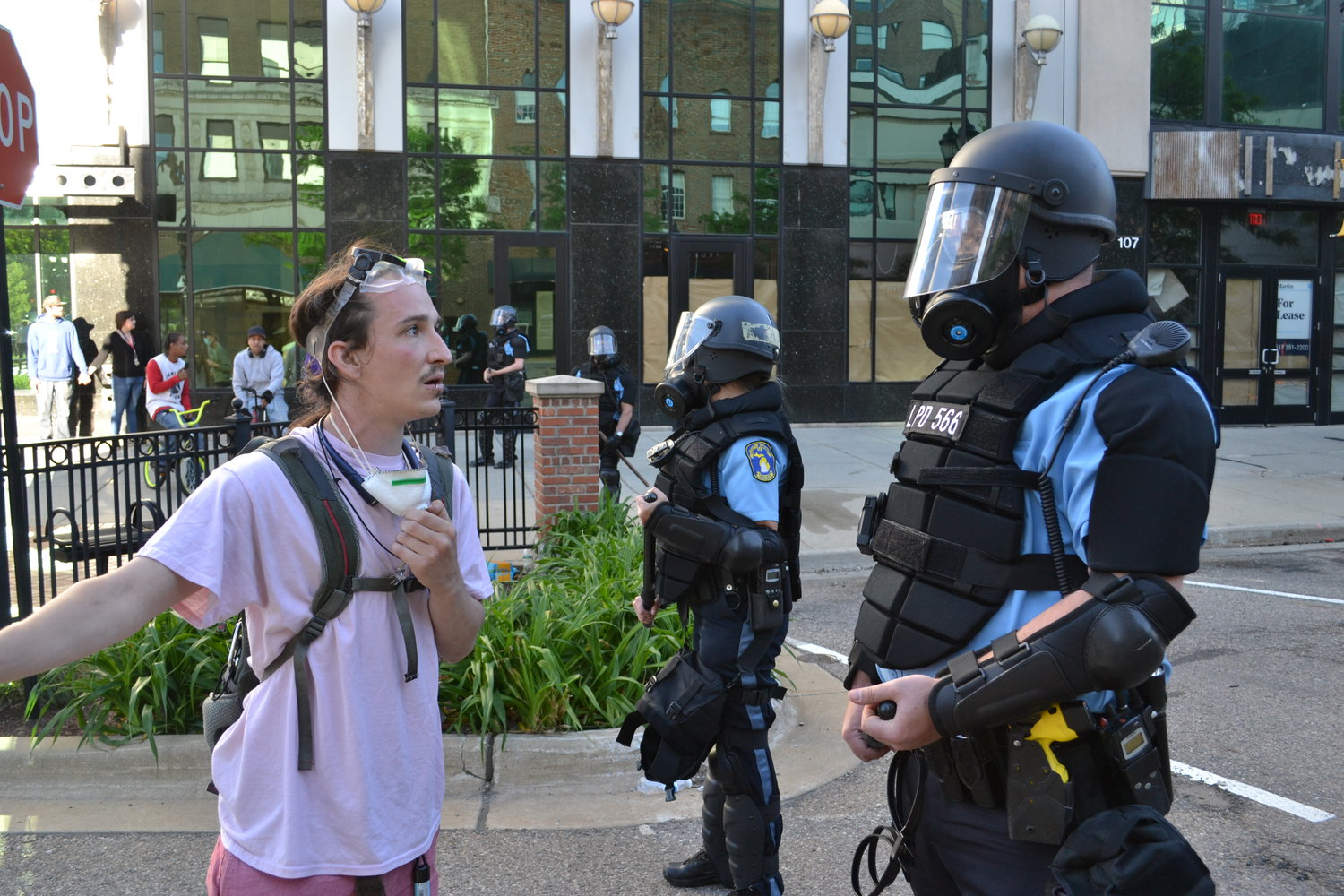 A protester speaks to a police officer in riot gear.