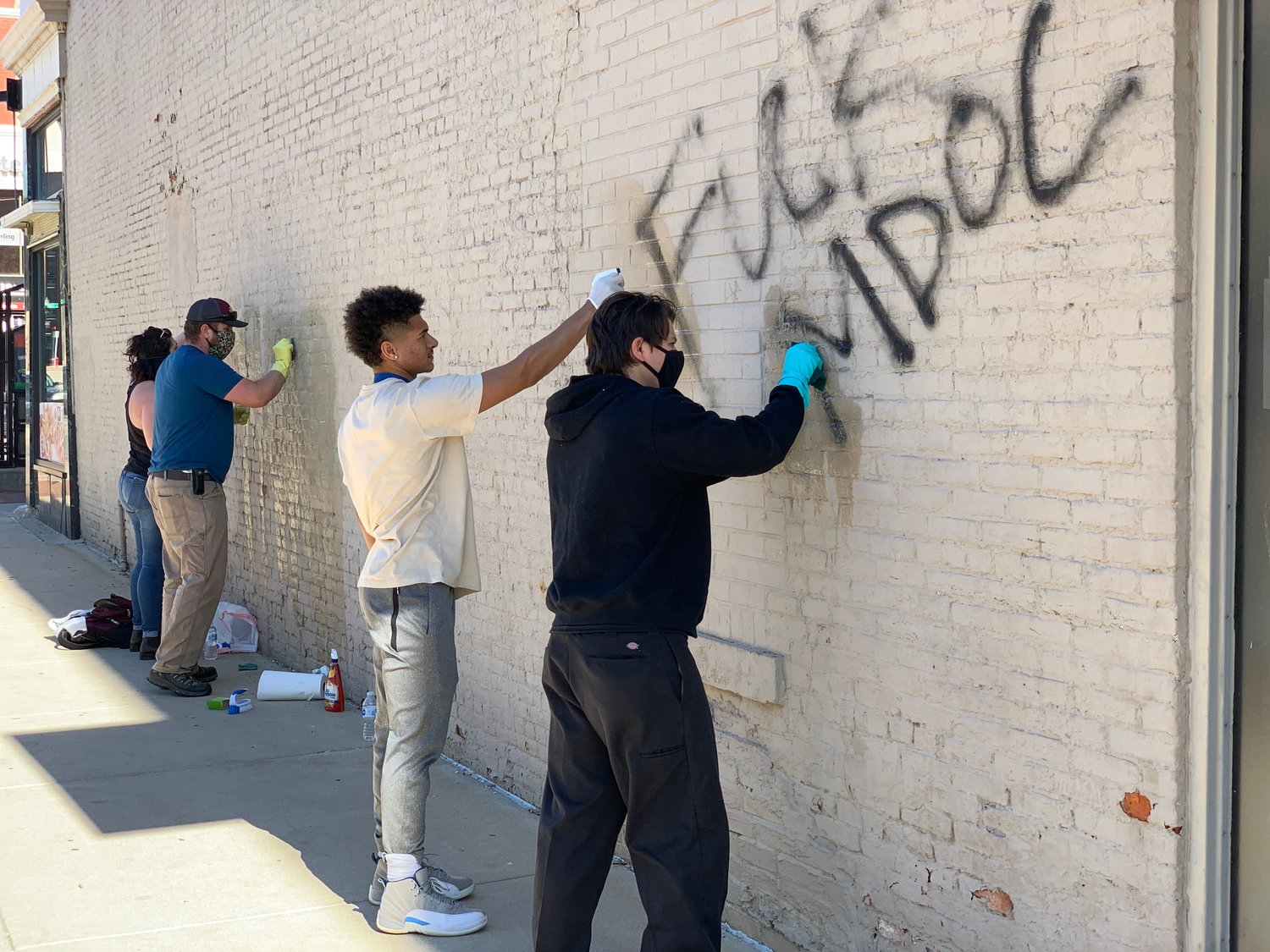 Volunteers scrub graffiti off a wall of a building this morning on Allegan Street between Washington Square and Grand Avenue as part of a clean up organized by Downtown Lansing Inc.