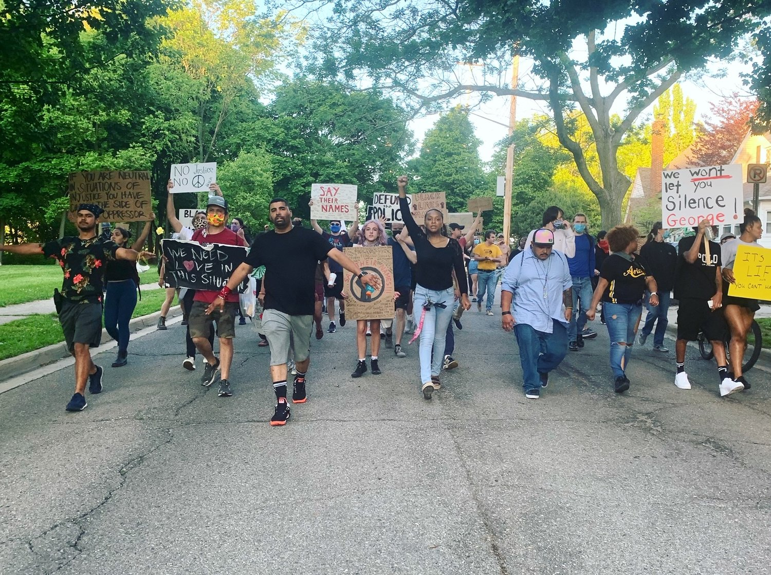 Protesters, led by Paul Birdsong, on Moores River Drive heading to Lansing Mayor Andy Schor's house.