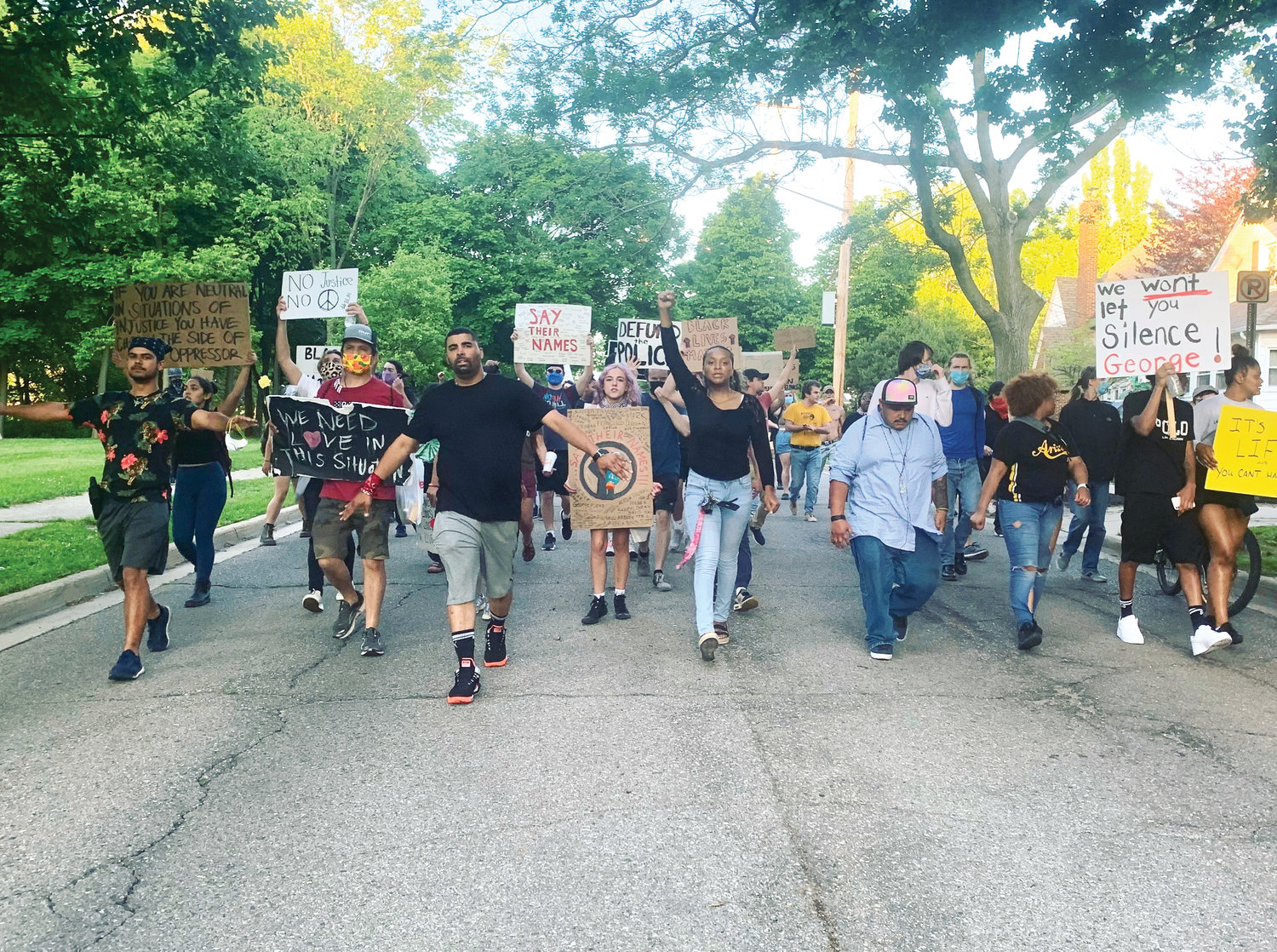 Paul Birdsong (left of center, black shirt) leads protesters in a march on Moores River Drive en route to Lansing Mayor Andy Schor's home.