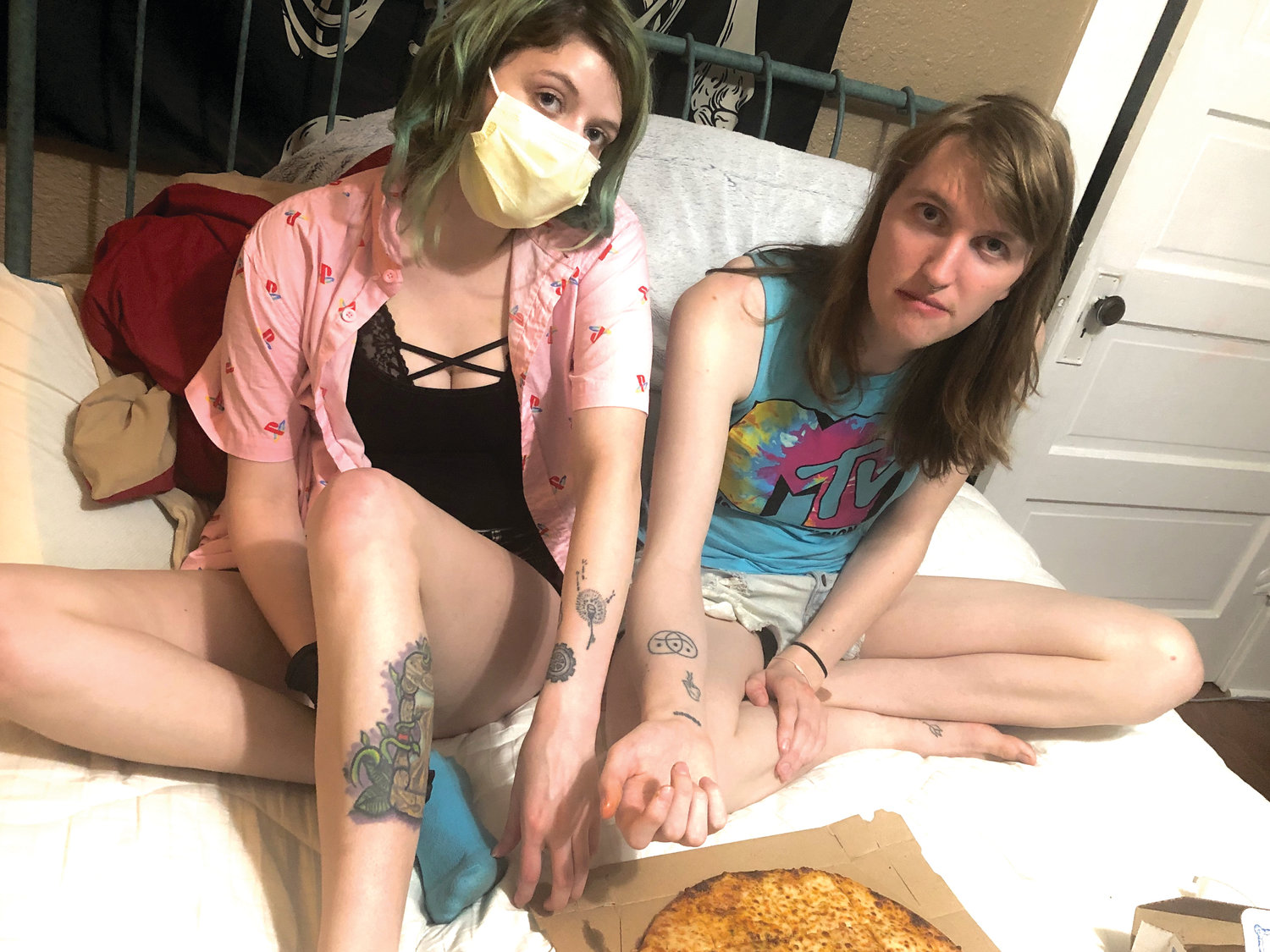Rowan Giffel (right) and their partner Emily Anderson show off their stick and poke tattoos while enjoying some pizza.