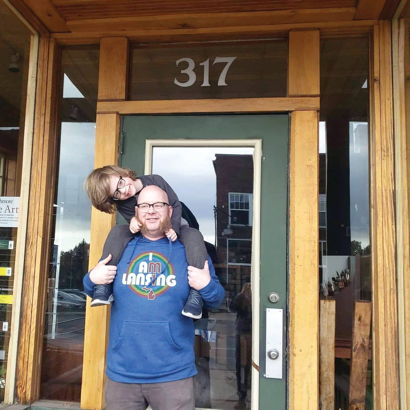 Odd Nodd Art Supply owner Casey Sorrow with his son in front of his new location at 317 Cesar E. Chavez Ave.