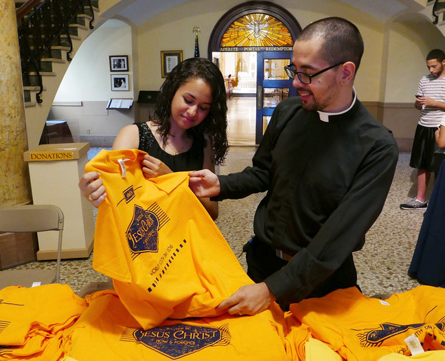 Father Adaly Rosado, parochial vicar at Incarnation parish in Washington Heights, and parishioner Cindy Rodriguez check out T-shirts that teens and young adults from the archdiocese will wear at World Youth Day in Krakow, Poland. They were at St. Joseph's Seminary in Dunwoodie July 14 for a Mass and blessing of pilgrims heading to the international gathering with Pope Francis, July 26-31. Story and photos on page 2; en Español, page 33.