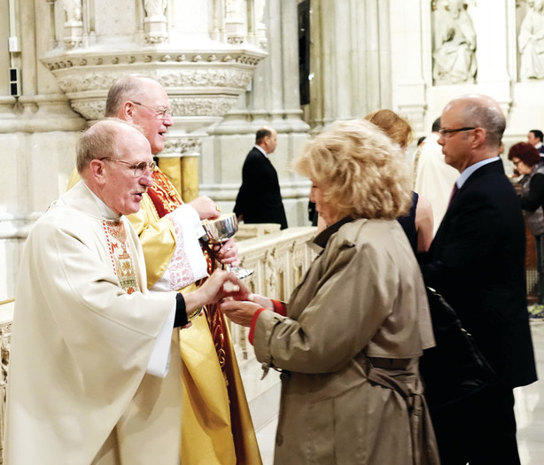 Cardinal Dolan and Father Joseph McShane, S.J., president of Fordham, distribute the Eucharist.